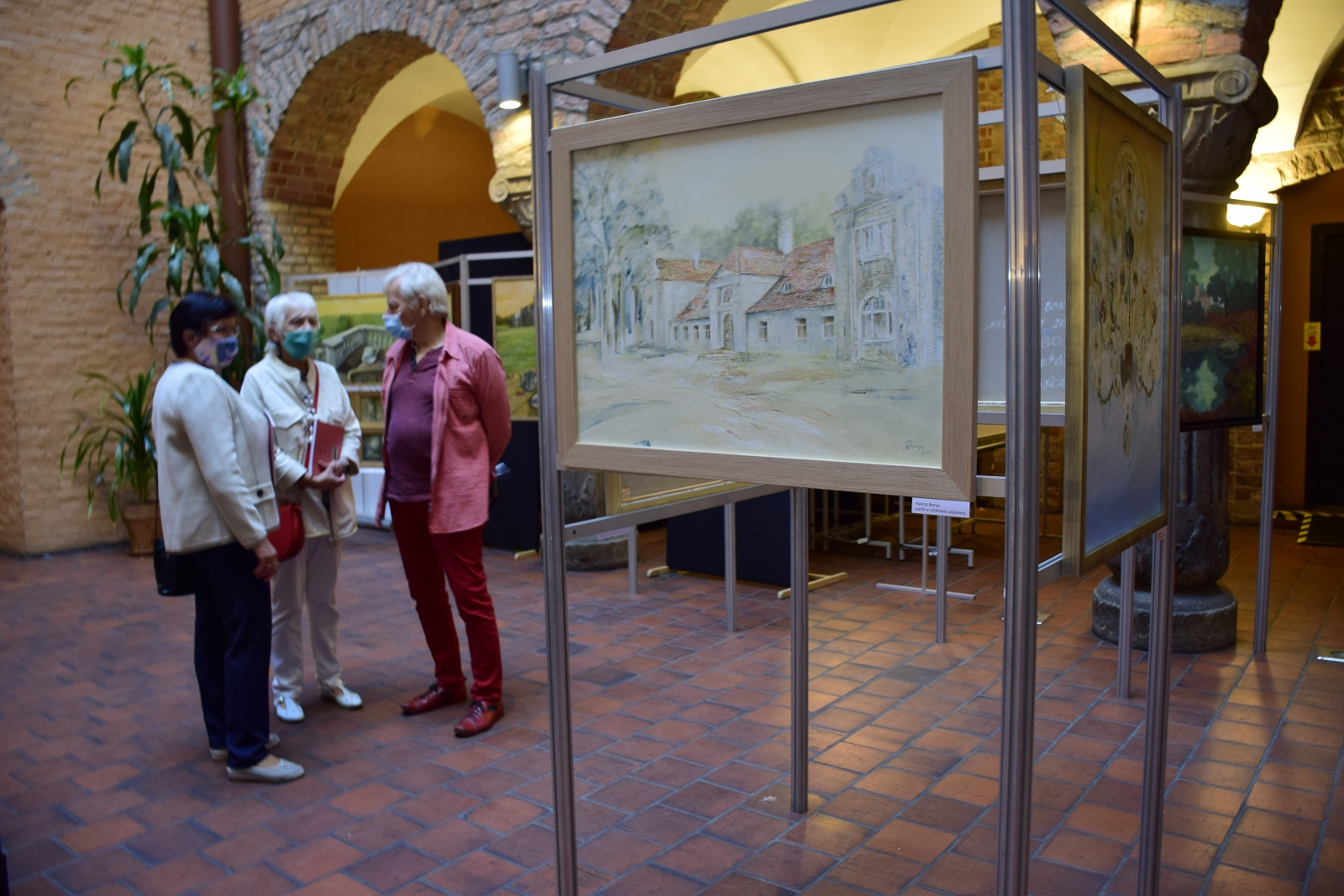 Na zdjęciu ukazany jest dziedziniec Muzeum Archeologicznego w Poznaniu, na którym ustawione zostały sztalugi z obrazami przedstawiającymi dwory i pałace. Dzieła są oglądane przez osoby uczestniczące w wernisażu.