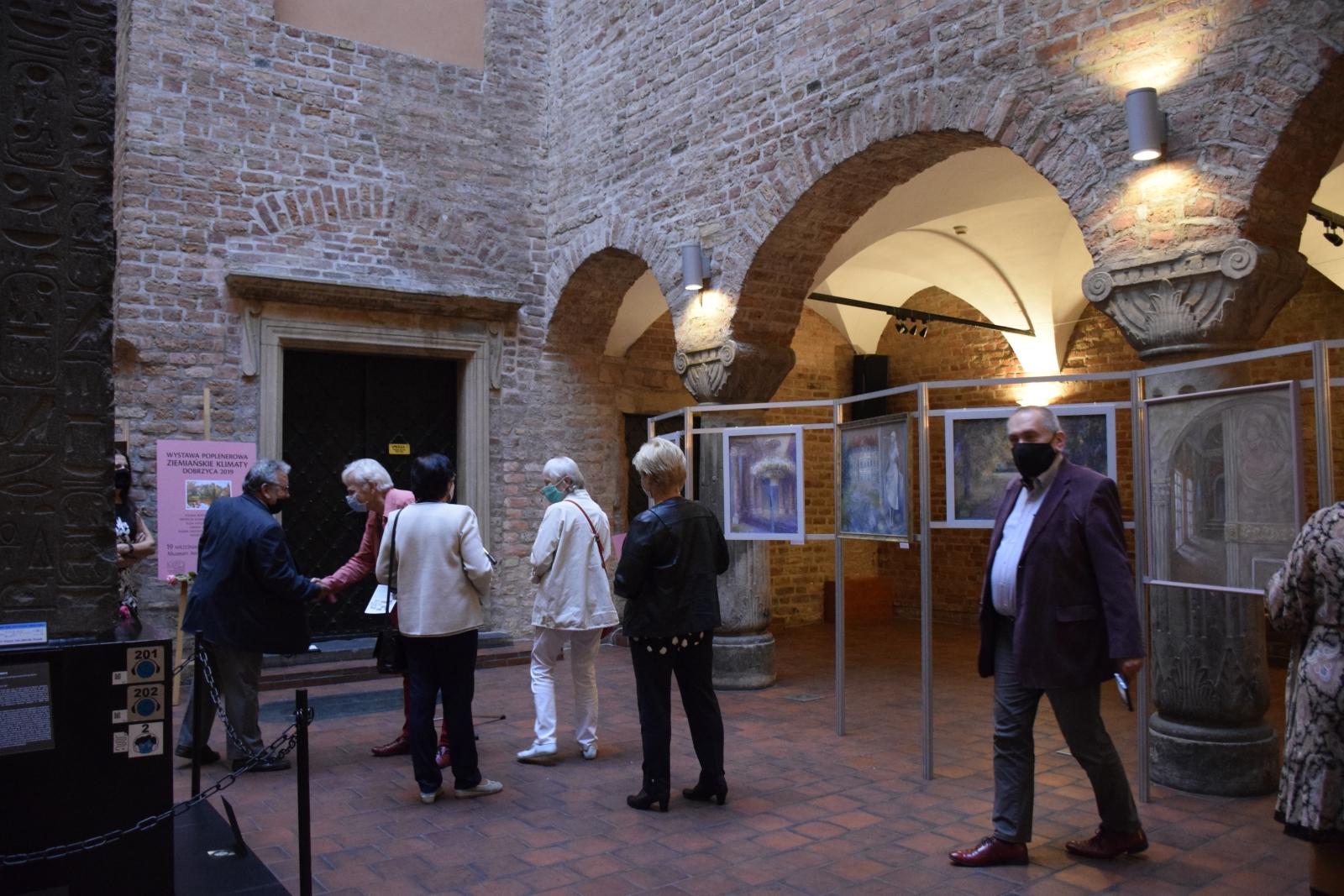 Na zdjęciu ukazane jest wnętrze dziedzińca Muzeum Archeologicznego w Poznaniu, na którym ustawione są sztalugi z obrazami przedstawiającymi dwory i pałace. Dzieła oglądane sa przez osoby uczestniczące w wernisażu.