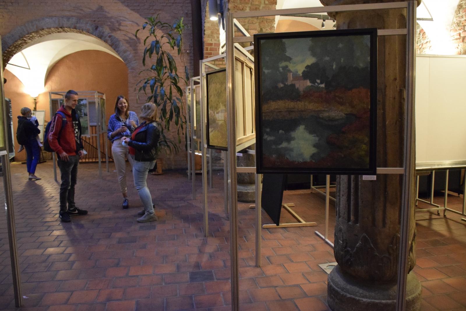 NA zdjeciu ukazany jest dziedziniec Muzeum Archeologicznego w Poznaniu, na którym ustawione sa sztalugi z obrazami przedstawiającymi dwory i pałace. Dzieła ogladane są przez osoby uczestniczące w wernisażu